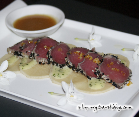 Seared tuna in black and white sesame with daikon slices, ginger sauce and jasmine flowers