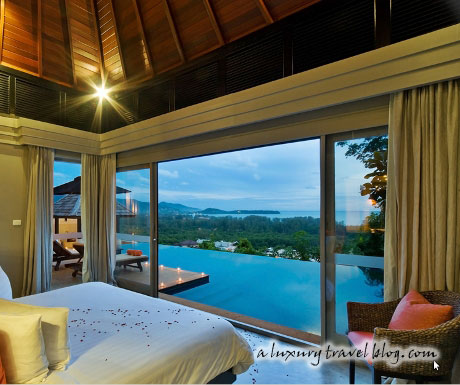 A bedroom with a view over an infinity pool and the sea beyond