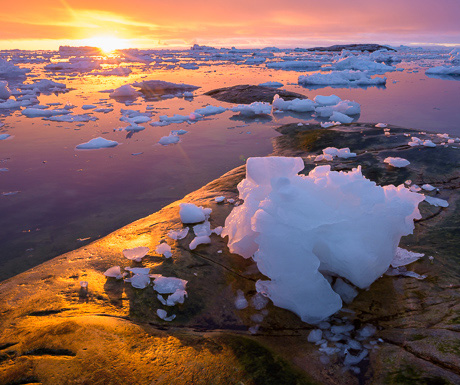 """Sunset over stranded """"growler"""" ice on the shore at Ilulissat, western Greenland"""