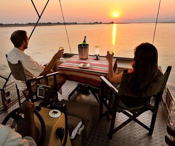 Couple enjoying sunset boat cruise at Chiawa Camp, Zambia