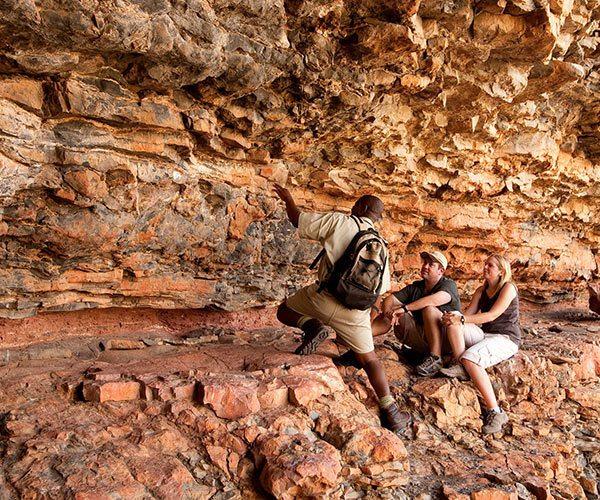 Guests looking at rock art, Sossusvlei Desert Lodge