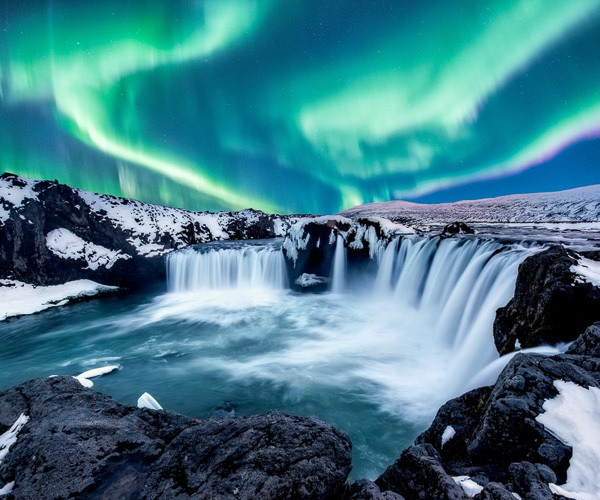 The magnificent Northern Lights above Godafoss waterfall in winter, North Iceland