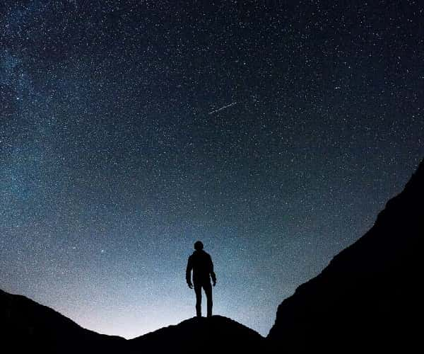 Stargazing in Wales, as man stands on mountain with stars in the sky